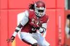 Arkansas' Alex Collins, left, looks to dodge Victor Hampton of South Carolina Saturday, Oct. 12, 2013, during the second quarter of the game against South Carolina at Donald W. Reynolds Razorback Stadium in Fayetteville.