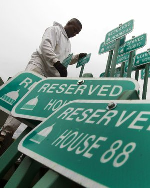 A worker sorts parking signs Wednesday outside the state Capitol in hasty preparation for today's arrival of legislators for the start of a special legislative session.