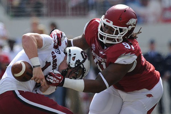 Arkansas tackle Darius Philon (91) causes South Carolina quarterback Connor Shaw to fumble the ball during the second quarter of play Saturday, Oct. 12, 2013, at Razorback Stadium in Fayetteville.