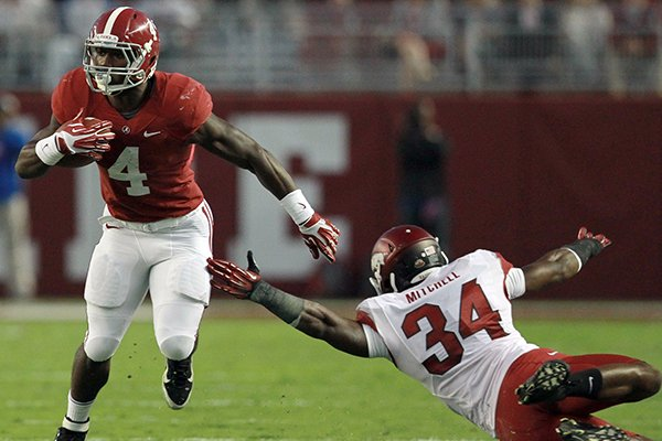 Alabama running back T.J. Yeldon (4) makes a move around Arkansas linebacker Braylon Mitchell (34) during the 1st half of the Razorbacks game in Alabama.