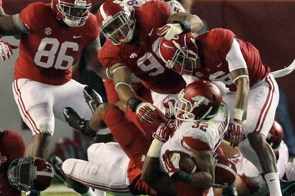 Arkansas running back Jonathan Williams (32) is brought down by Alabama defenders Saturday at Bryant-Denny Stadium in Tuscaloosa, Ala.