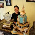 Jennifer Matsubara, owner of Shelby Lynn's Cake Shoppe in Springdale, stands next to the cake that r...