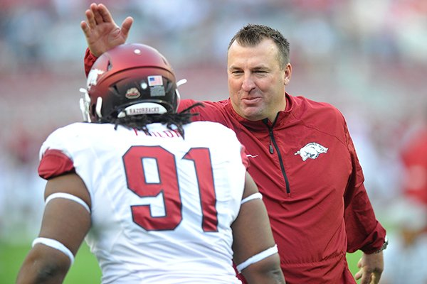 Arkansas coach Bret Bielema talks with defensive lineman Darius Philon prior to an Oct. 19, 2013 game against Alabama at Bryant-Denny Stadium in Tuscaloosa, Ala.