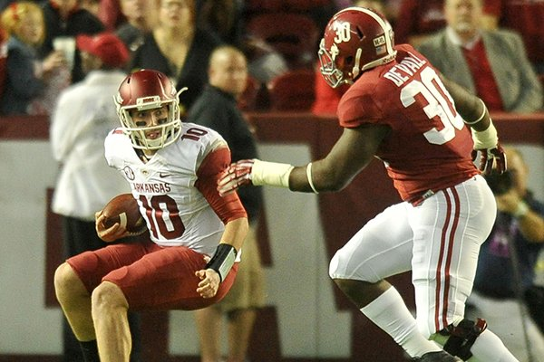 Arkansas quarterback Brandon Allen (10) scrambles away from Alabama linebacker Denzel Devall (30) in the 1st quarter of an Oct. 19, 2013 game at Bryant-Denny Stadium in Tuscaloosa, Ala.