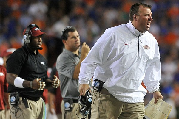 Arkansas coach Bret Bielema and assistant coaches Charlie Partridge and Taver Johnson yell to players from the sideline during an Oct. 6, 2013 game against Florida at Ben Hill Griffin Stadium in Gainesville, Fla.