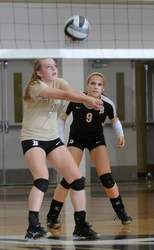 Kayton Coffee, right, watches as her teammate Emily Bruce, both from Bentonville, passes the ball Tuesday, Oct. 1, 2013, during the game against Siloam Springs at Tiger Arena in Bentonville. The Lady Tigers swept the Lady Panthers of Siloam Springs, 3-0.