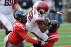Arkansas' Jonathan Williams, center, is taken down by Ole Miss' Lavon Hooks, left, and Channing Ward Saturday, Nov. 9, 2013, during a halfback pass in the third quarter of the game against Ole Miss at Vaught-Hemingway Stadium in Oxford, Miss.