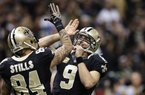 New Orleans Saints quarterback Drew Brees (9) celebrates with wide receiver Kenny Stills (84) after a touchdown pass in the second half of an NFL football game in New Orleans, Sunday, Nov. 10, 2013. (AP Photo/Dave Martin)
