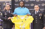 El Dorado News-Times/Michael Orrell -- Army Sgt. 1st Class Halbert Lee, left, and Sgt. 1st Class Chris Chavir present El Dorado High School football player Bijhon Jackson with his U.S. Army All-American Bowl jersey in front of family, coaches, teammates, classmates and friends in the Wildcat Arena. Jackson was officially invited on Monday, as one of only 90 high school seniors to play in the bowl game that will take place on January 4, 2014 in San Antonio, Texas.