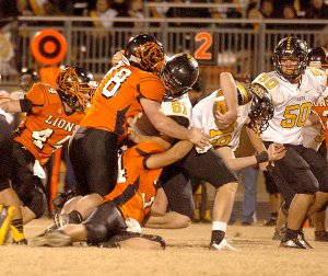 Photo by Randy Moll  Gravette's Tyler Kerley (#34) and Jacob Taylor (#78) take down Prairie Grove's quarterback, Jacob Storlie, as he crosses the line of scrimmage, while Prairie Grove's Jackson Diebold (#61) blocks and Connor West (#50) looks on during play in Lion Stadium on Friday night. Gravette's Cody Robinson (#44) is at the left.