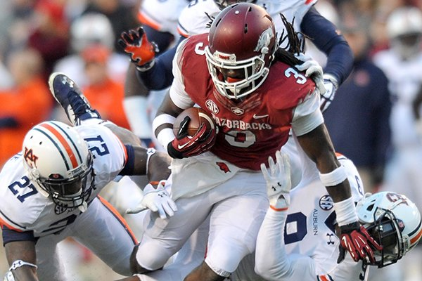 University of Arkansas running back Alex Collins is taken down by Auburn defenders Robenson Therezie and Jermain Whitehead during the second quarter of Saturday night's game at Razorback Stadium in Fayetteville.