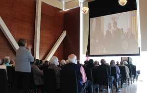 Attendees at a viewing party for the Presidential Medal of Freedom ceremony watch as President Bill Clinton receives his medal. The Clinton Presidential Center in Little Rock hosted the watch party.