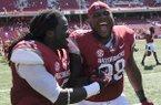 Arkansas running back Alex Collins, left, and defensive tackle Robert Thomas celebrate Saturday, Sept. 14, 2013, after the Hogs' win at Razorback Stadium in Fayetteville.