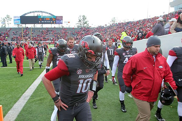 Arkansas quarterback Brandon Allen leave the field after a disappointing overtime loss to Mississippi during their game Saturday at War Memorial Stadium in Little Rock. Allen threw an interception to end the game.