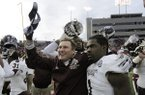 Mississippi State coach Dan Mullen, celebrates Mississippi State's 24-17 overtime victory over Arkansas with defensive back Nickoe Whitley (1) after the NCAA college football game in Little Rock, Ark., Saturday, Nov. 23, 2013. (AP Photo/David Quinn)
