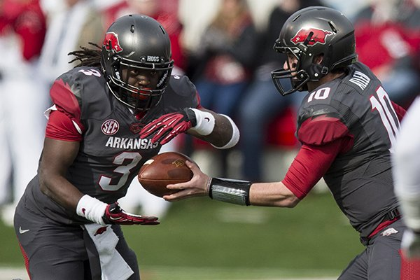 Alex Collins receives a hand off from QB Brandon Allen during their game against Mississippi State on Nov. 23, 2013 at War Memorial Stadium in Little Rock.
