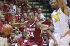 Arkansas guard Michael Qualls (24) attempts to drive the baseline while being defended by California forward Richard Solomon (35) in the second half of an NCAA college basketball game at the Maui Invitational on Monday, Nov. 25, 2013, in Lahaina, Hawaii. California defeated Arkansas 85-77. (AP Photo/Eugene Tanner)