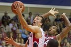 Gonzaga guard Kevin Pangos (4) slips between Arkansas guard Michael Qualls, top right, and guard Fred Gulley III (12) to shoot a layup in the first half of an NCAA college basketball game at the Maui Invitational on Wednesday, Nov. 27, 2013, in Lahaina, Hawaii. (AP Photo/Eugene Tanner)