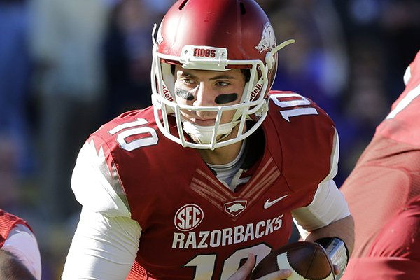 Arkansas quarterback Brandon Allen (10) drops back in the first half of an NCAA college football game against LSU in Baton Rouge, La., Friday, Nov. 29, 2013. (AP Photo/Bill Haber)