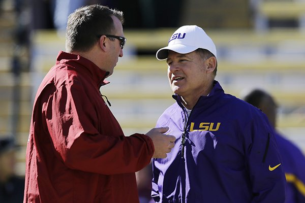 LSU head coach Les Miles talks with Arkansas head coach Brett Bielema before the start of an NCAA college football game against in Baton Rouge, La., Friday, Nov. 29, 2013. (AP Photo/Bill Haber)