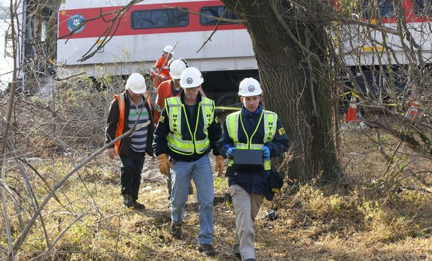 in-this-dec-1-2013-photo-provided-by-the-national-transportation-safety-board-safety-board-investigators-mike-hiller-center-left-and-george-haralampopoulous-right-walk-with-an-data-recorder-retrieved-from-the-derailed-metro-north-train-in-the-bronx-borough-of-new-york-two-data-recorders-from-the-commuter-train-that-derailed-while-rounding-a-riverside-curve-killing-four-people-may-provide-information-on-the-speed-of-the-train-how-the-brakes-were-applied-and-the-throttle-setting-a-member-of-the-ntsb-said-monday-dec-2-2013