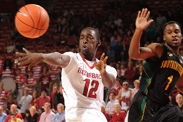 Arkansas guard Fred Gulley III (12) passes out of the lane as Southeastern Louisiana guard Dre Evans defends during the first half of play Tuesday, Dec. 3, 2013, in Bud Walton Arena in Fayetteville.
