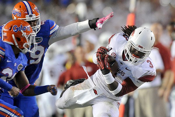 Arkansas running back Alex Collins pulls in a pass past Florida defender Darin Kitchens during the third quarter of a Saturday, Oct. 5, 2013 game at Ben Hill Griffin Stadium in Gainesville, Fla.