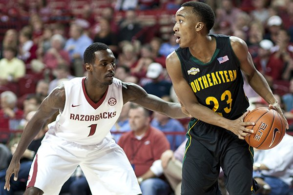 Southeastern Louisiana's Joshua Filmore (23) looks to pass the ball as Arkansas' Mardracus Wade (1) defends during the first half of an NCAA college basketball game in Fayetteville, Ark., Tuesday, Dec. 3, 2013. (AP Photo/Sarah Bentham)