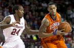 Clemson forward K.J. McDaniels, right, drives to the basket against Arkansas guard Michael Qualls during the first half of a NCAA college basketball game against Clemson Saturday, Dec. 7, 2013, at Bud Walton Arena in Fayetteville, Ark. (AP Photo/Gareth Patterson)