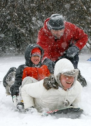 Darin Phelan gives his wife Jessica and son Lucas,6, a push Friday as they begin there tandem slide down the snow covered hill north of Reynolds Razorback Stadium in Fayetteville. The Phelans, which with daughter Kennedy, 8, and son Tyler, 10, got an early start on the snow-driven activities.