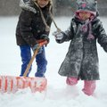 Jocelyn Trejo, 7, left, and Pamela Trejo, 4, shovel snow Friday outside their apartment in Springdal...