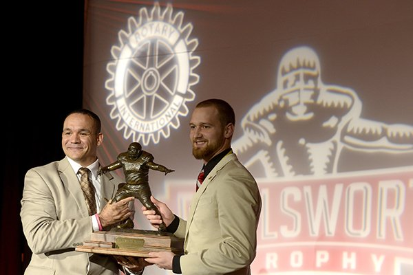 Jared Abbrederis, right, senior wide receiver for the University of Wisconsin, accepts the Burlsworth Trophy from Robert Smith, ESPN football analyst, Monday, Dec. 9, 2013 during the trophy ceremony at the Northwest Convention Center in Springdale. The award, presented by the Springdale Rotary Club, is given an outstanding college football player who started as a walk-on.