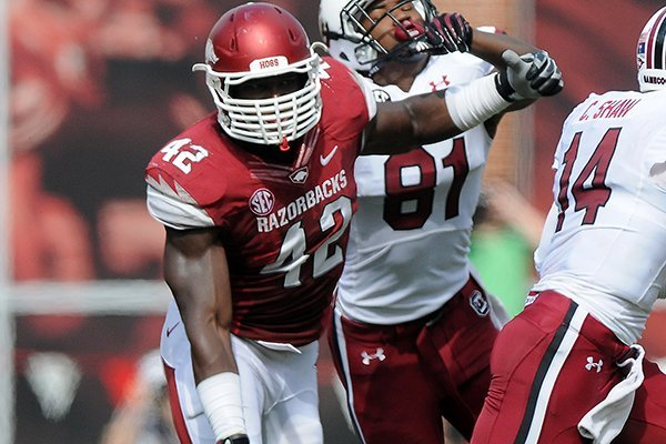 Arkansas's Chris Smith, left, charges after Connor Shaw of South Carolina Saturday, Oct. 12, 2013, during the second quarter of the game against South Carolina at Donald W. Reynolds Razorback Stadium in Fayetteville.