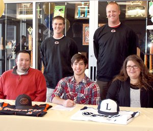 Photo by Dodie Evans Wyatt Gibbons, center, is flanked by his parents, Tim and Stephanie Gibbons, as he signs to play baseball with the Lyon College Scots. GHS baseball coach Randall Hunt, left, a...
