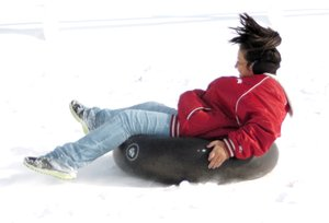 Photo by Randy Moll Lania Perez, 11, rides an inner tube down a snow-covered hill in Gentry on Saturday, Dec. 7, 2013....