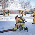 STAFF PHOTO SPENCER TIREY Springdale firefighter Nathan Warrell, center, rolls a hose as Division Ch...