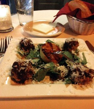 The Grilled Meatballs, an appetizer at Ristorante Capeo, comes with a balsamic vinegar reduction on a bed of dandelion greens.