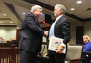University of Arkansas trustee John Goodson, left, shakes hands with former fundraising division chief Brad Choate Friday after Goodson addressed a legislative audit panel.