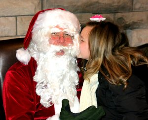 Photo by Randy Moll Alandrea Roberson leans over and gives Santa a kiss during his visit to the Gentry Chamber of Commerce building on Saturday.