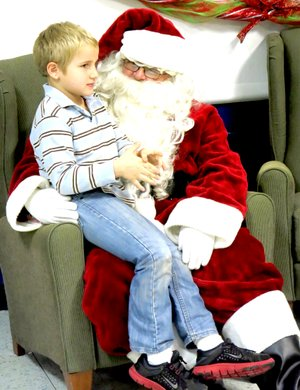 Photos by Mike Eckels A young boy visited with Santa Claus during the Decatur Christmas Festival on Dec. 14 in the high school cafeteria. The youngster was relaying his Christmas list to the jolly old elf himself.