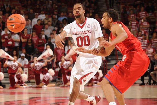 Arkansas guard Rashad Madden (00) passes around Southern Methodist guard Nick Russell during the first half of play Monday, Nov. 18, 2013, in Bud Walton Arena in Fayetteville.