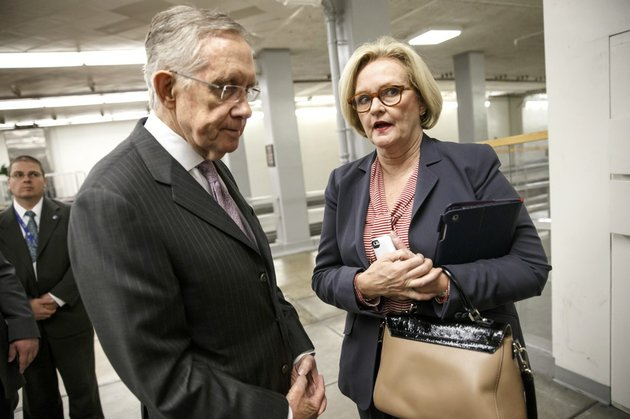 senate-majority-leader-harry-reid-of-nev-speaks-to-sen-claire-mccaskill-d-mo-right-on-capitol-in-washington-tuesday-dec-17-2013-as-lawmakers-come-and-go-from-the-senate-after-a-bipartisan-budget-compromise-cleared-a-procedural-hurdle-advancing-past-a-filibuster-threshold-on-a-67-33-vote-that-ensures-the-measure-will-pass-the-democratic-led-chamber-no-later-than-wednesday-and-head-to-the-white-house-to-be-signed-into-law-when-enacted-the-measure-would-ease-for-two-years-some-of-the-harshest-cuts-to-agency-budgets-required-under-automatic-spending-curbs-commonly-known-as-sequestration