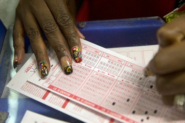a-woman-fills-out-a-form-to-buy-a-mega-millions-ticket-at-the-gallery-shop-in-washington-tuesday-dec-17-2013-the-mega-millions-jackpot-soared-to-an-estimated-636-million-on-tuesday-making-it-the-second-largest-lottery-jackpot-in-us-history