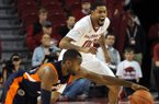 Arkansas's Rashad Madden, right, and UT Martin's DeMarc Richardson chase after the ball after it got loose from Richardson during the first half of the basketball game in Bud Walton Arena in Fayetteville on Thursday December 19, 2013.