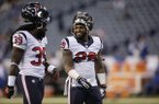 Houston Texans running backs Deji Karim, left, talk Dennis Johnson before an NFL football game against the Indianapolis Colts in Indianapolis, Sunday, Dec. 15, 2013. (AP Photo/AJ Mast)