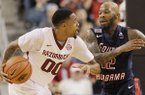 South Alabama's Antoine Allen (12) defends Arkansas' Rashad Madden (00) in the second half of an NCAA college basketball game in North Little Rock, Ark., Saturday, Dec. 21, 2013. Arkansas defeated South Alabama 72-60. (AP Photo/Danny Johnston)