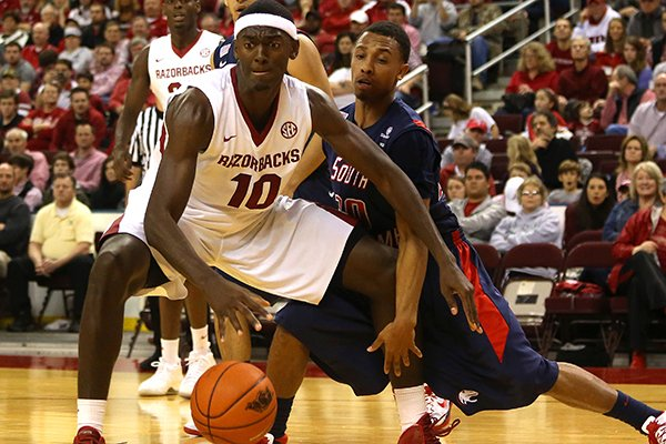 Arkansas' Bobby Portis dribbles before a lay up as South Alabama's Aakim Saintil defends during their game at Verizon Arena December 21, 2013.