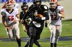 Charleston quarterback Ty Storey (4) runs away from Glen Rose defenders Scott Kehner (22) and Justin Salazar (56) during Saturday night's Class 3A state final at War Memorial Stadium in Little Rock.  Special to the Arkansas Democrat Gazette/Jimmy Jones