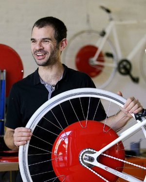 In this Thursday, Dec. 12, 2013 photo, Assaf Biderman, co-inventor of the Copenhagen Wheel and Associate Director of the SENSEable City Laboratory at MIT, poses with his invention at Superpedestrian, his venture-backed company in Cambridge, Mass. The Copenhagen Wheel is a human/electric hybrid bicycle engine built into a bicycle's back wheel. Pre-orders for the Copenhagen Wheel are being taken with delivery expected by May 2014. (AP Photo/Stephan Savoia)