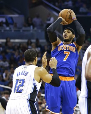 New York Knicks' Carmelo Anthony (7) shoots over Orlando Magic's Tobias Harris (12) in the first half of an NBA basketball game in Orlando, Fla., Monday, Dec. 23, 2013. (AP Photo/John Raoux)